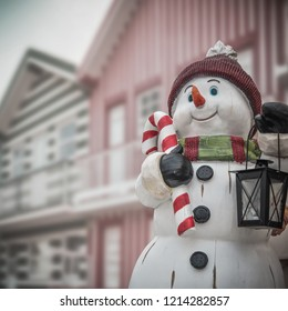 Funny snowman in christmas scene with colorful houses