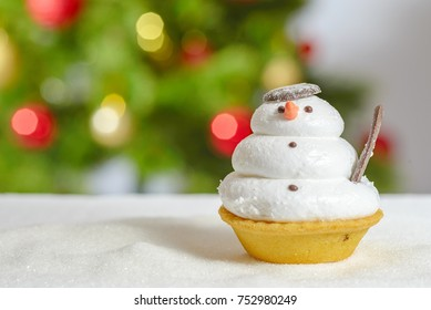 funny Snowman cookie with snow and christmas tree behind.