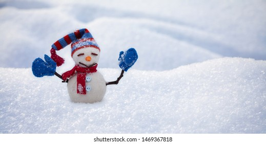 Funny snowman with hat red scarf and blue mittens, natural snowy field background. Happy New Year and Merry Christmas postcard template. copy space