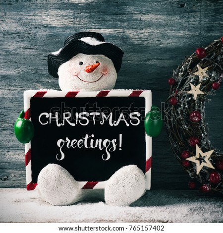 Funny snowman holding black signboard text stock photo edit now a funny snowman holding a black signboard with the text christmas greetings written in it m4hsunfo