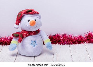 Funny snowman in a red hat and scarf on a white wooden background