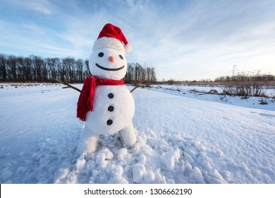 Funny snowman in santa hat and red scalf on snowy field. Christmass and New Year background