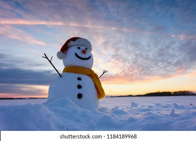 Funny snowman in Santa hat and yellow scalf on snowy field. Merry Christmass and happy New Year!
