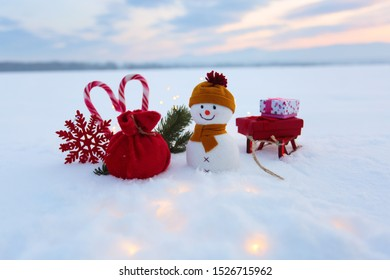 Funny snowman with sledges and colorful boxes with presents. Garlands enlighten the snow. New Year and Christmas concept with snowy background. Winter scenery.