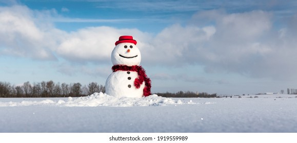 Funny snowman in stylish red hat and red scalf on snowy field. Panoramical photo ideal for site head mockup