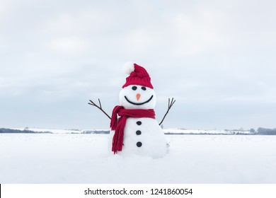 Funny snowman in stylish santa hat and red scalf on snowy field