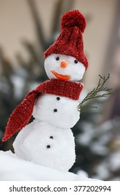 Funny snowman wrapped scarf with woolen cap on snow covered coniferous tree background, concept of winter season