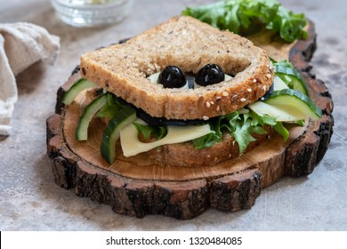 Funny spider sandwich with black cheese and olives for Halloween party, scary food