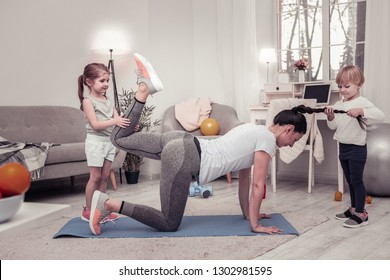 Funny sport with children. Children disturbing their mother doing exercises