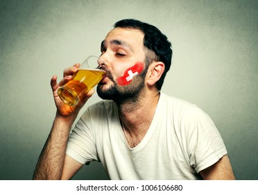 Funny sport fan with flag painted on face drinking beer