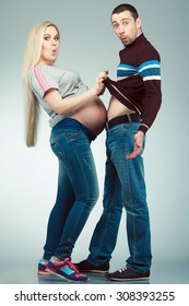 Funny sport training of future parents concept. Full length portrait of married couple touching bellies of each other, posing over gray background. Sporty style. Studio shot