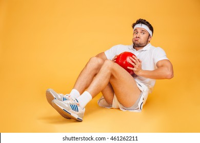 Funny sports man working out with fitness ball isolated on a orange background