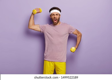 Funny sportsman raises arms with dumbbells, shouts emotionally, feels strong and sporty, dressed in purple t shirt and yellow shorts, stands indoor. Man works out in gym, does exercises. Bodybuilding
