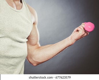 Funny sporty fit man lifting light dumbbell weight. Closeup of muscular strong guy training. Bodybuilding exercise fun.