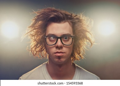 Funny Squinting man with Tousled brown hair in studio using spotlights in background