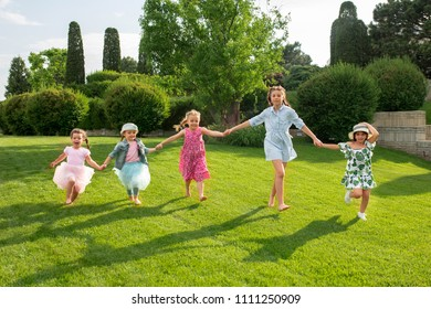 Funny starts. Kids fashion concept. The group of teen boys and girls running at park. Children colorful clothes, lifestyle, trendy colors concepts.