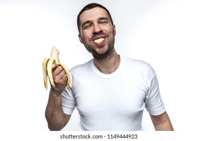 Funny and strange man is eating banana. He is enjoying that. Man is eating banana in a funny manner. His behave is like a small boy has. Isolated on white background.
