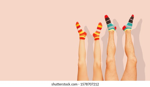 Funny striped socks. Legs of a married couple. Isolated on the Coral Pink