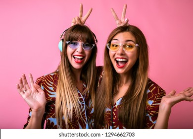Funny studio portrait of two pretty funny woman going crazy together, wearing bright trendy clothes and glasses, tropical pijamas, party mood.