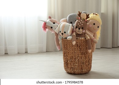 Funny stuffed toys in basket on floor, space for text. Children's room interior decor