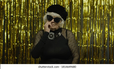 Funny stupid senior old woman picking nose with silly brainless humorous expression, removing boogers, uncultured habit, bad manners. Elderly stylish lady grandma on golden background