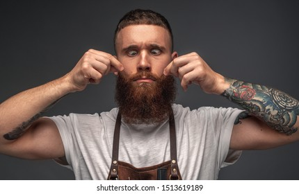 Funny stylish bearded barber in apron grimacing showing imaginary mustache on face with tattooed hands and squinting eyes to nose