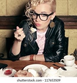 funny stylish blonde girl with great hairdo, glasses, black jacket eating cake in cafe. indoor shot