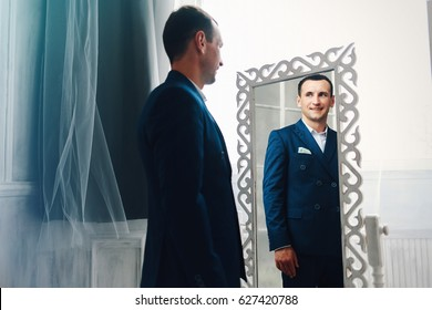 Funny stylish man in a blue suit looks in the mirror.
