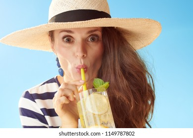 funny stylish woman in straw hat against blue sky drinking refreshing cocktail