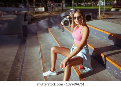 Funny stylish young woman skater with cruiser board and retro tape recorder sits on stairs in skatepark