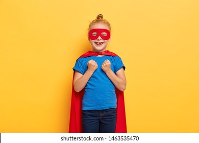 Funny superheroine girl clenches fists, celebrates successful fight with evil, pretends defending universe being cartoon character wears special costume has special magical power extraordinary ability