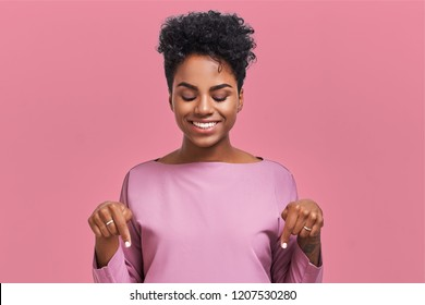 Funny surprised African American female looks with joyful eyes down and indicates as shows something, sees comic things, isolated over pink wall. Positive amazed young woman poses in studio.