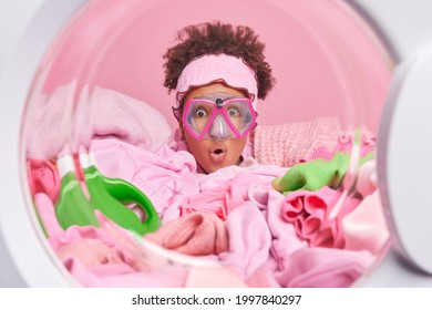 Funny surprised female housewife with curly hair wears snorkeling mask poses in washer circle with laundry and detergent around. Clothes to be washed in automatic washing machine. Laundering concept