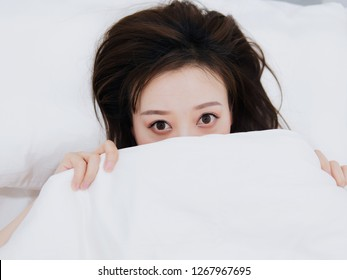 Funny surprised girl covering half of face with white blanket, young scared woman hiding and peeking from duvet, afraid of night monsters, feels embarrassed, wide awake, head shot close up, top view.