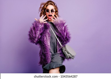 Funny surprised girl in fashionable attire screaming on purple background. Studio shot of stylish caucasian woman with little gray purse having fun during photoshoot.Place for text