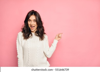 funny surprised girl showing empty copy space with her finger