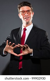 Funny talking business man with grey suit and red tie isolated on dark background. Wearing vintage glasses. Studio shot.