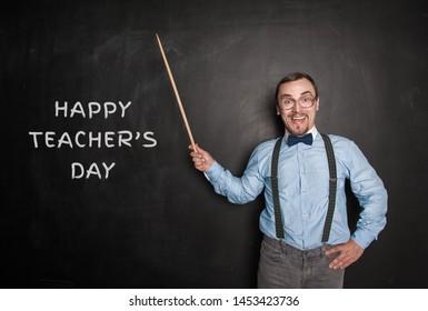 Funny teacher man with pointer on blackboard. Happy teachers day