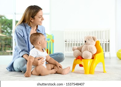 Funny teddy bear sitting on potty and mother with her child at home
