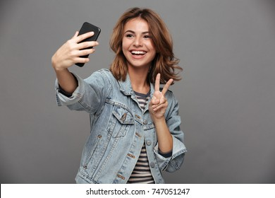 Funny teen girl in jeans jacket showing peace gesture while taking selfie on smartphone, isolated on gray background