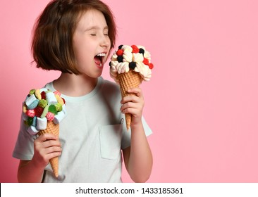 Funny teen girl kid eating licking biting a big ice cream in waffles cone with tasty toppings raspberry marshmallow marmalade while holding another one ready on pink background