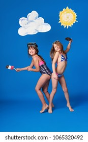 Funny teen girls wear stylish bikini, swimwear for beach, pool, happy summer day. Fashion kids girlfriends indulge, laugh on blue background,studio. Concept vacations,travel,recreation. full length.