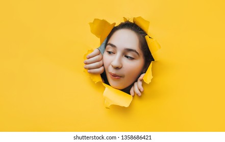 Funny teenage girl peeping through hole on yellow paper. The concept of surprise, joyful mood from what he saw. Discounts, sales, surprise. Copy space.