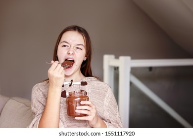 Funny teenager girl enjoying eating chocolate cfream from glass jar at home. Stop diet. Giving up dieting. Unhealthy food.
