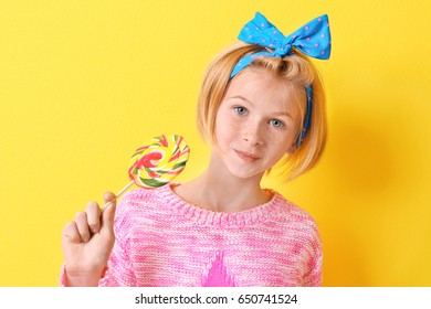 Funny teenager girl holding colourful lollipop on yellow background