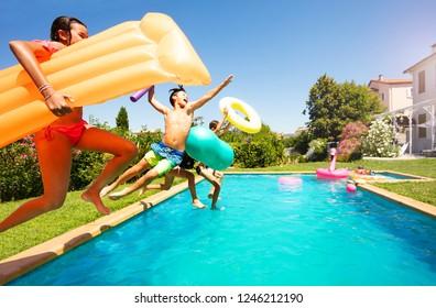 Sonnige Zwiebeln mit Schwimmgeräten, die in den Pool springen