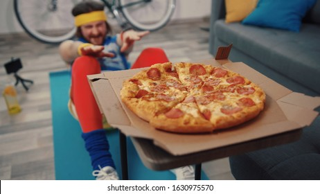 Funny tense sportsman making crunches on exercise mat trying to reach pizza. Junk food and sport concept.