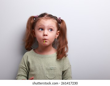 Funny thinking kid girl eating lollipop and looking up on grey background