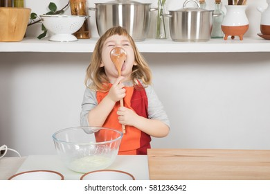 funny three years old child with orange and red apron making and cooking a sponge cake at kitchen home, licking yogurt in wooden spoon looking