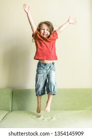 Funny three-year-old child jumps on couch. Happy little girl playing and jumping at home. Adorable toddler with long hair dances on sofa. Joyful kid in red jumping in the room.